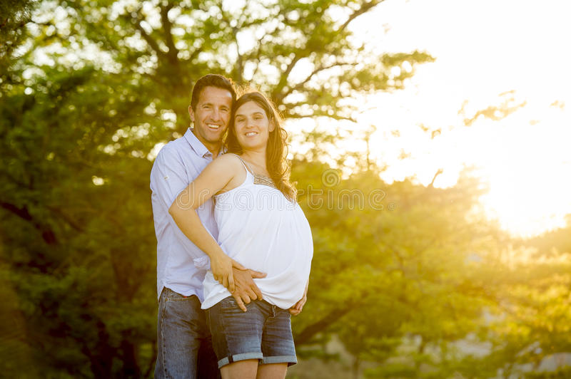 Happy couple in love together in park landscape on sunset with woman pregnant belly and man. Young happy beautiful couple in love walking together on grass and royalty free stock photos