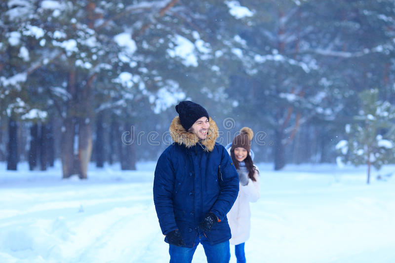 Happy couple in love walking in the winter woods stock photography