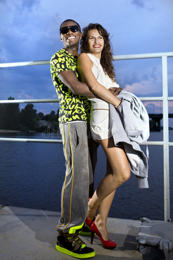 Happy couple of lovers. In harbour at night, afro-american man embraces caucasian woman stock image