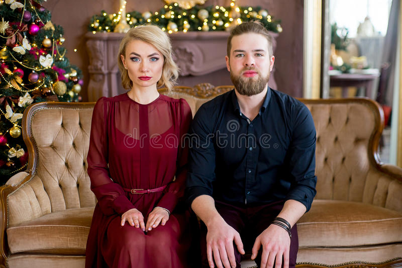 Happy couple of lovers. Christmas. Happy couple of lovers with serious faces. Christmas tree and new year gift at home. Young family together stock images