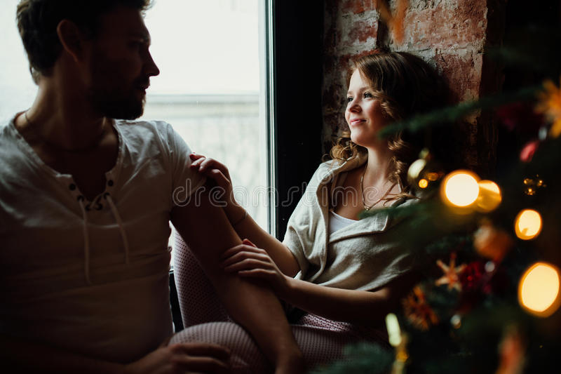 Happy couple of lovers in pajamas sit on the windowsill. Christmas atmosphere. Happy couple of lovers in pajamas sit on the windowsill. Christmas atmosphere and stock photos