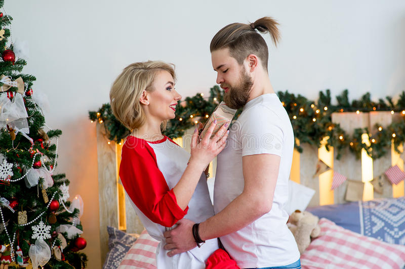Happy couple of lovers playing on the bed. Christmas tree and New Year at home. Young family together royalty free stock photo