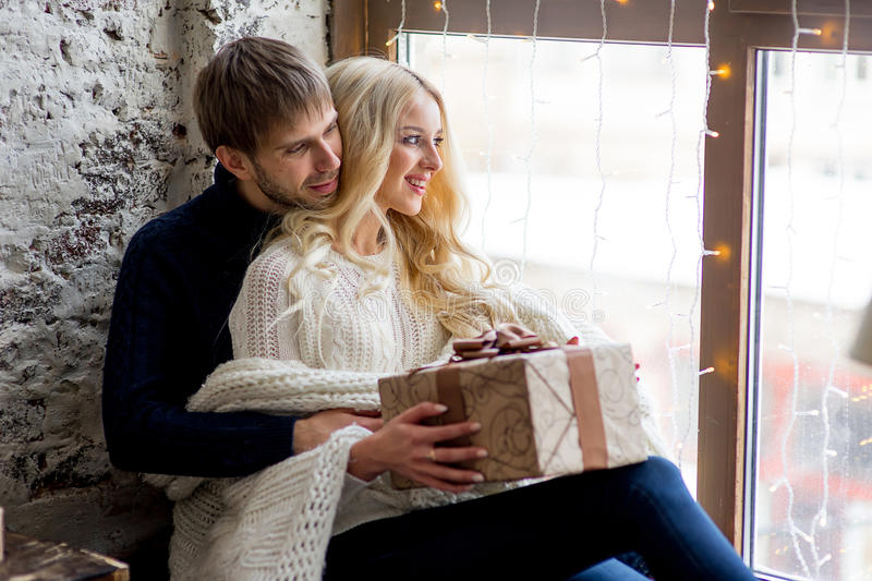 Happy couple of lovers in pullovers give each other gifts sitting. On the windowsill. Christmas and new year gift at home. Young family together royalty free stock image