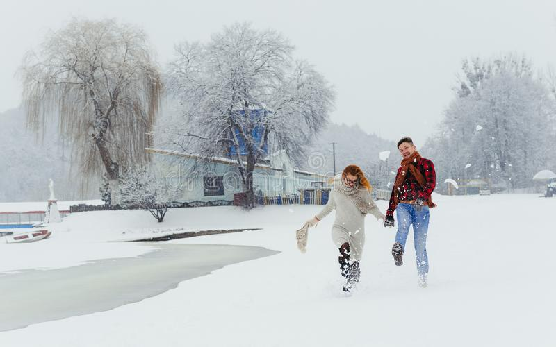 Happy couple of lovers is spending time on the snowy meadow. They are walking during the snowfall. Christmas fairytale. stock images