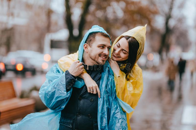 Happy couple loving guy and his girlfriend dressed in raincoats are hugging on the street in the rain royalty free stock photography