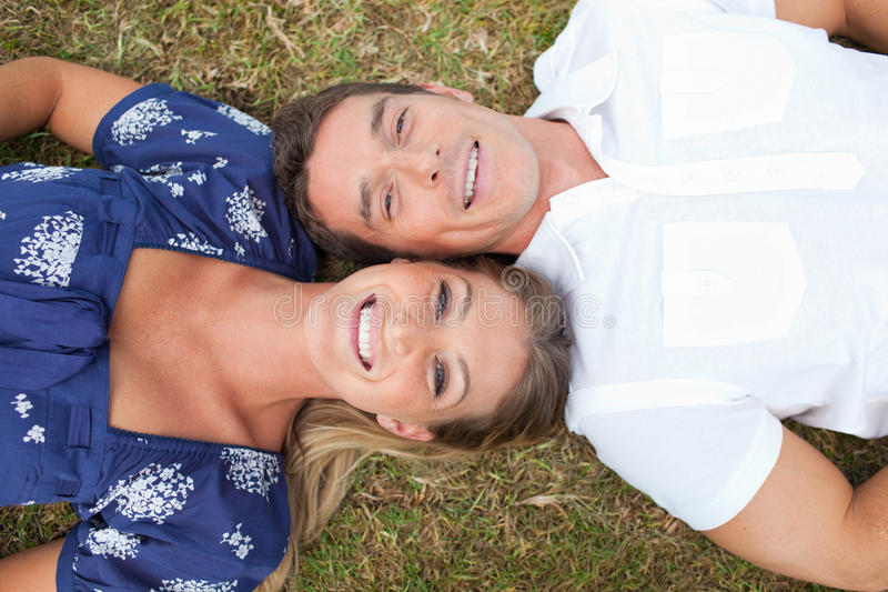 Happy couple lying on the grass. In a park stock photography
