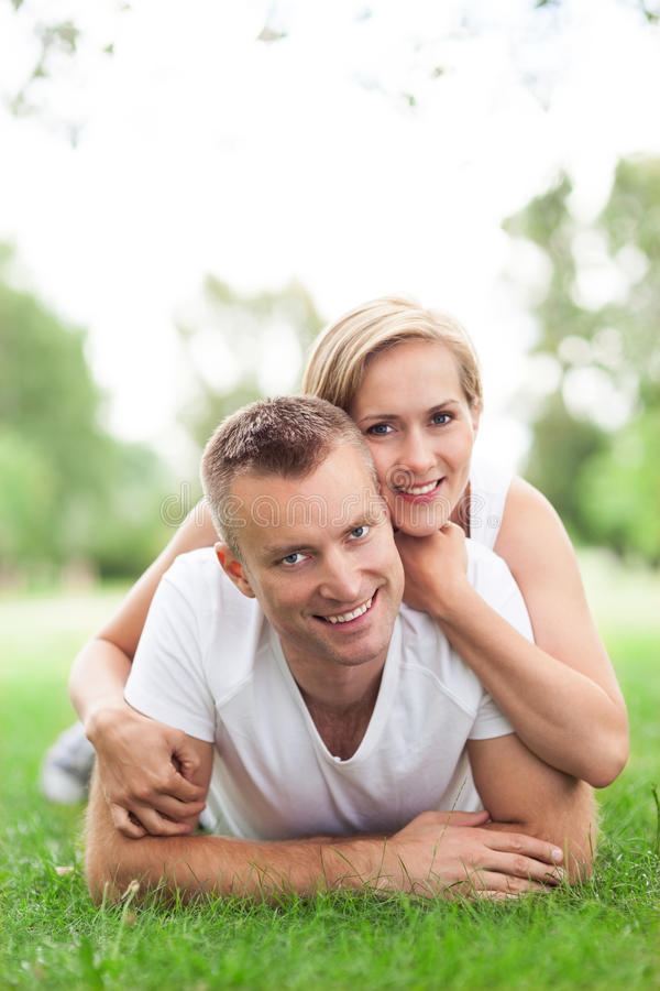 Happy Couple Lying On Grass Stock Photo