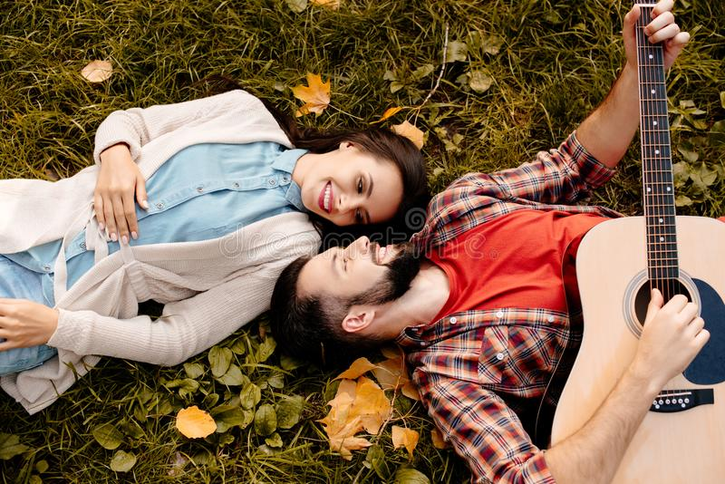 Happy couple lying on grass in autumn park while boyfriend. Playing the guitar royalty free stock images