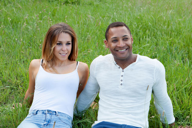 Happy couple lying on the grass in the field. Thinking about his future royalty free stock photography