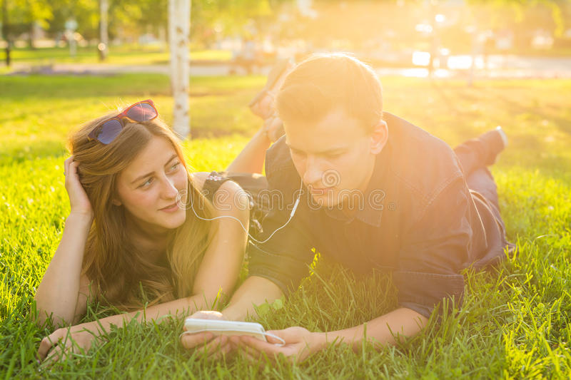 Happy couple lying on the grass and resting together, having fun outdoor. Portrait of funny lovers.  royalty free stock photography