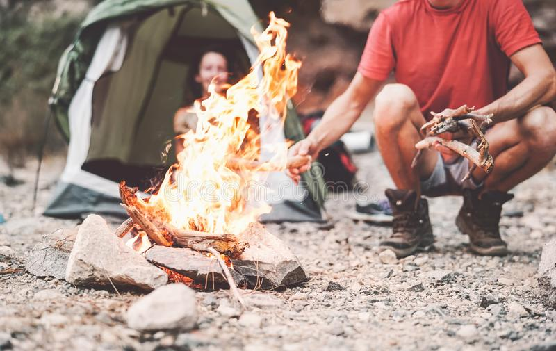 Happy couple making fire while camping in wild forest - Young people having fun traveling and camping next bonfire royalty free stock photo