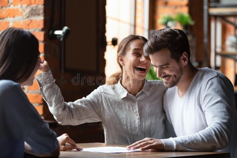 Happy couple making successful deal in cafe, purchase real estate. Smiling wife and husband taking loan or mortgage with good conditions, businesswoman royalty free stock photos