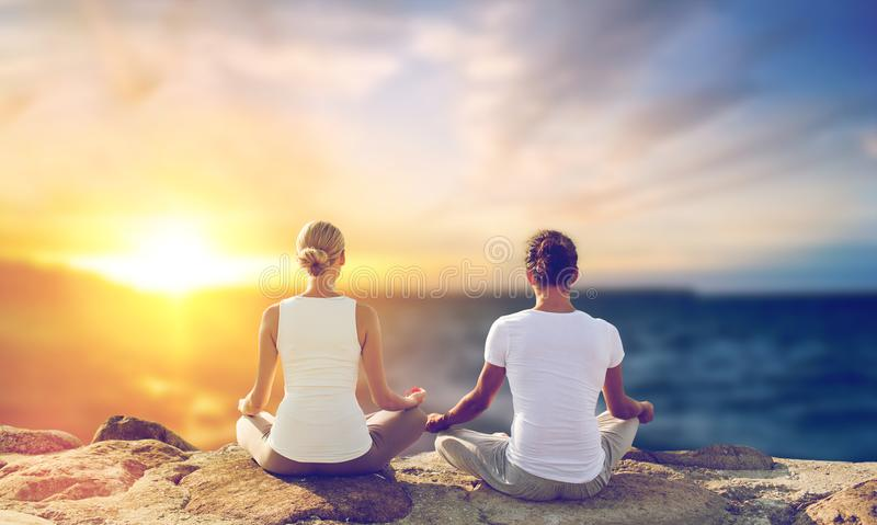 Happy couple making yoga and meditating outdoors royalty free stock photos