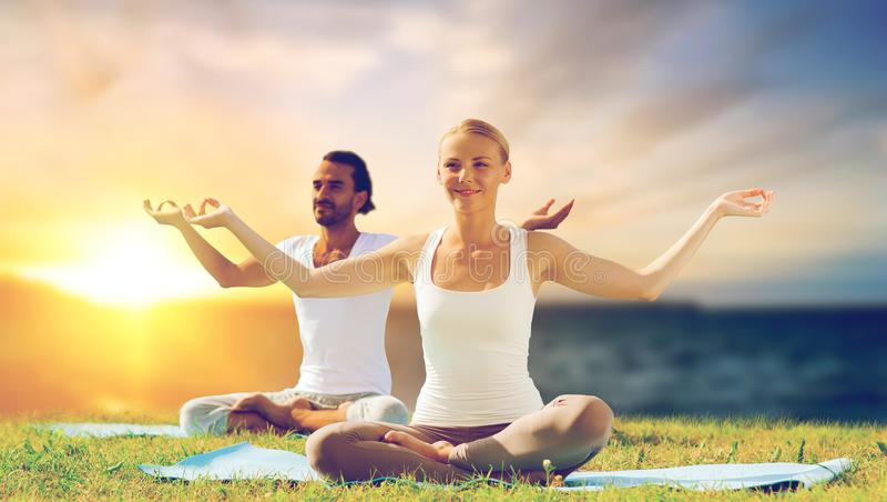 Happy couple making yoga and meditating outdoors royalty free stock photo
