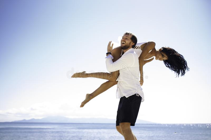 Happy couple, man raised his girlfriend on the shoulder, isolated on beach, blue water, sunny day. Vacantion in Greece. stock photos