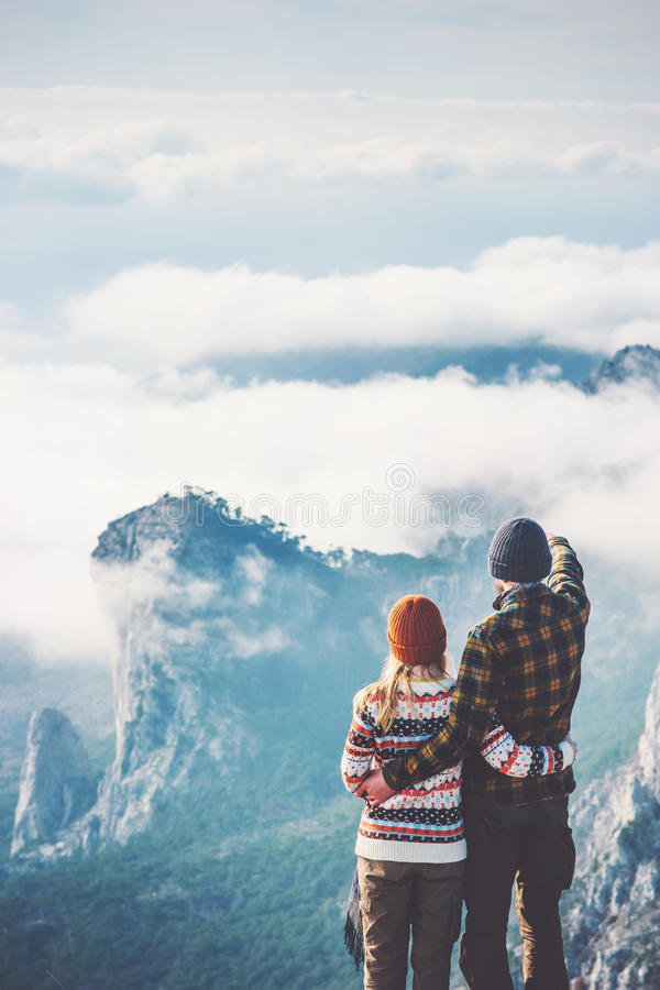 Happy Couple Man and Woman hugging enjoying mountains. And clouds landscape on background Love and Travel emotions Lifestyle concept. Young family traveling stock photography