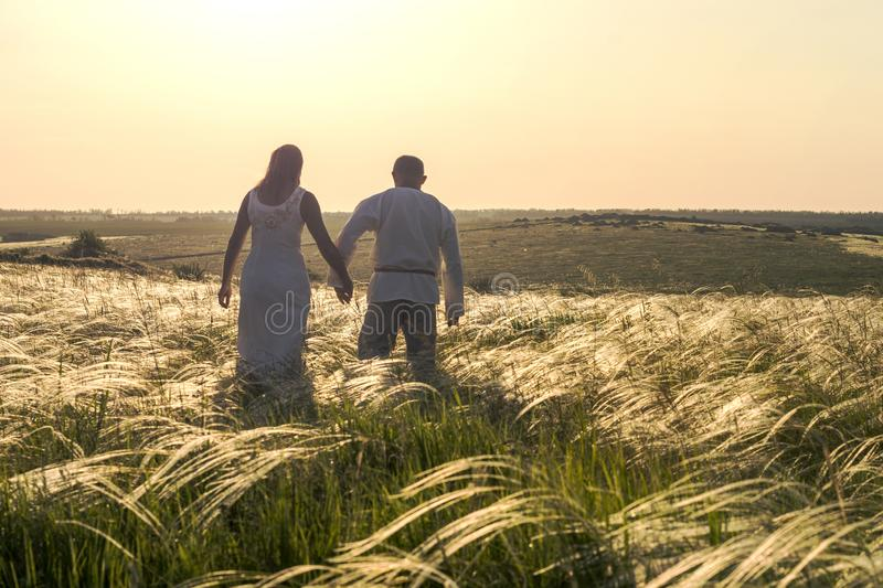 Happy couple man and woman in national Slavic clothes walking in field on sunset and holding hands. Welcome to Russia stock photos