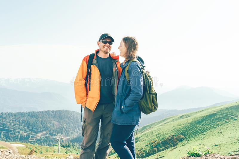 Happy couple man and woman on a peak in the mountains royalty free stock photography
