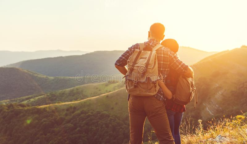 Happy couple man and woman tourist at top of mountain at sunset. Happy couple men and women tourist at top of mountain at sunset outdoors during a hike in summer stock images