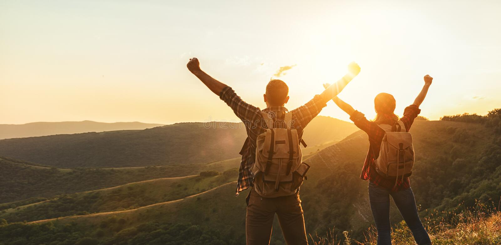 Happy couple man and woman tourist at top of mountain at sunset royalty free stock image