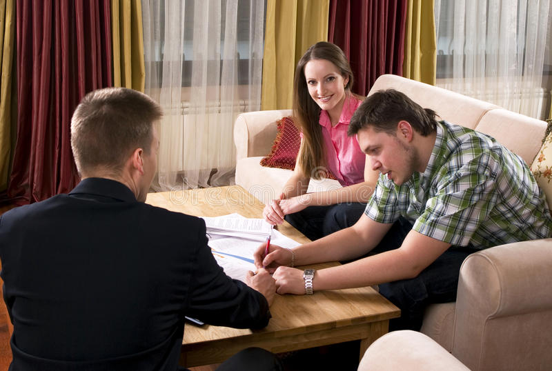 Happy couple meeting with agent at home royalty free stock photography