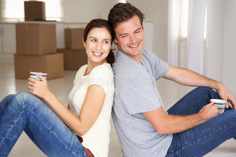 Happy couple in new home. Smiling sitting back to back stock photography