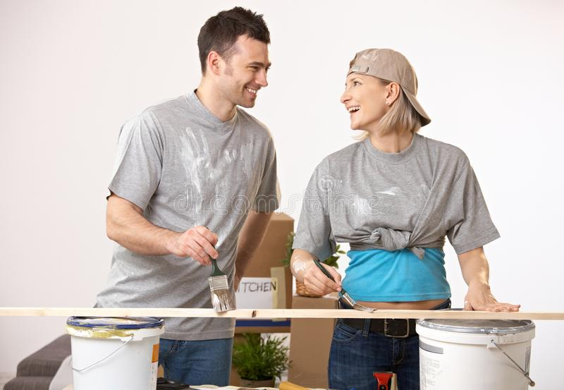 Happy couple at new home having fun painting. Happy casual caucasian couple at new home having fun painting. Smiling, looking at each other, standing royalty free stock photo