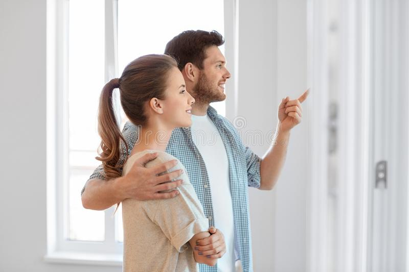 Happy couple at new home. Mortgage, people and real estate concept - happy couple at new home stock image