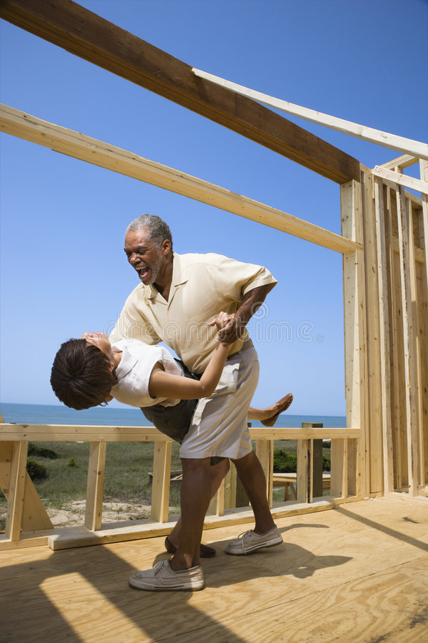 Happy couple at new home site. African American middle aged couple dancing in new home construction at beach