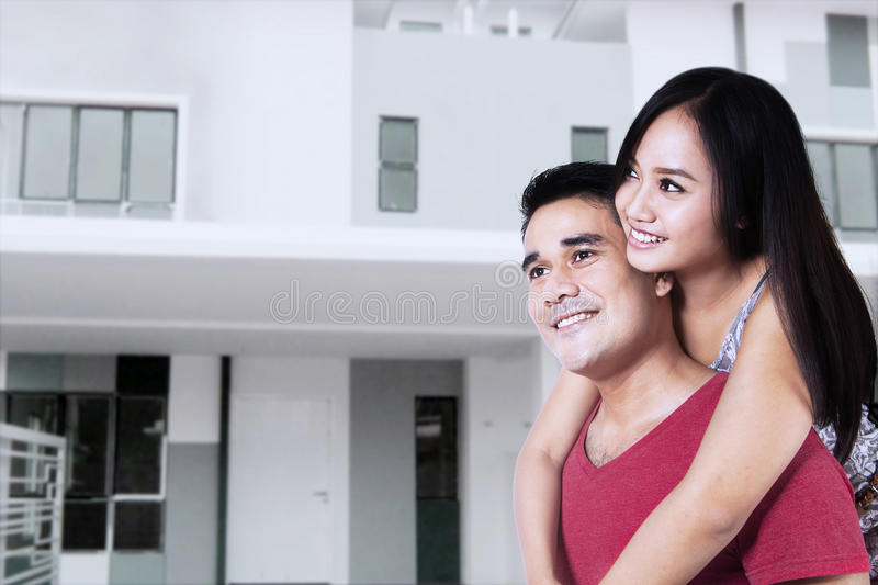 Happy couple with new home. Happy smiling young couple with a new home royalty free stock photo