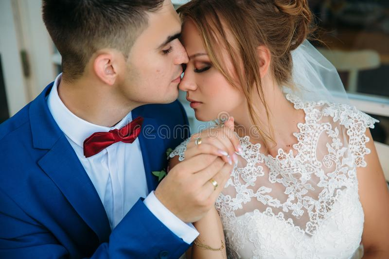 A happy couple of newlyweds gently embrace each other. A man with trembling holds the hand of his bride. The girl closed stock photography