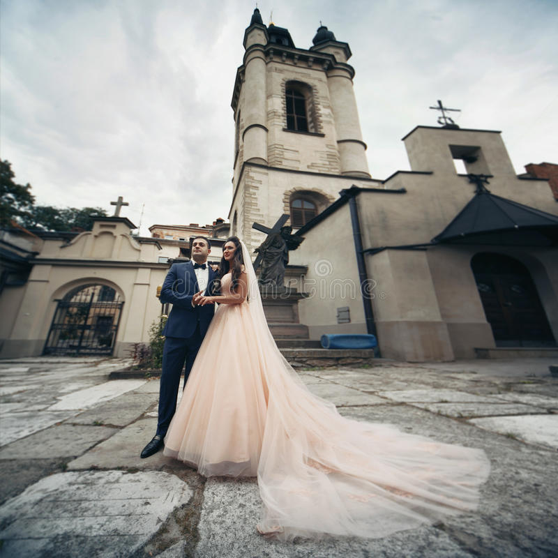 Happy couple of newlyweds holding hands with an old church in Lviv in the background stock photo