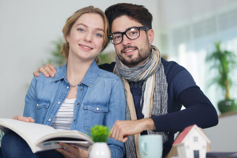 Happy couple next to house miniature stock image