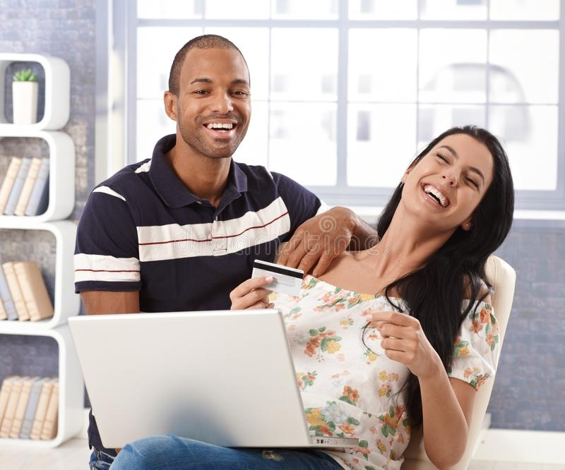 Happy couple online shopping at home laughing. Happy interracial couple shopping online at home, using credit card, laughing stock photography