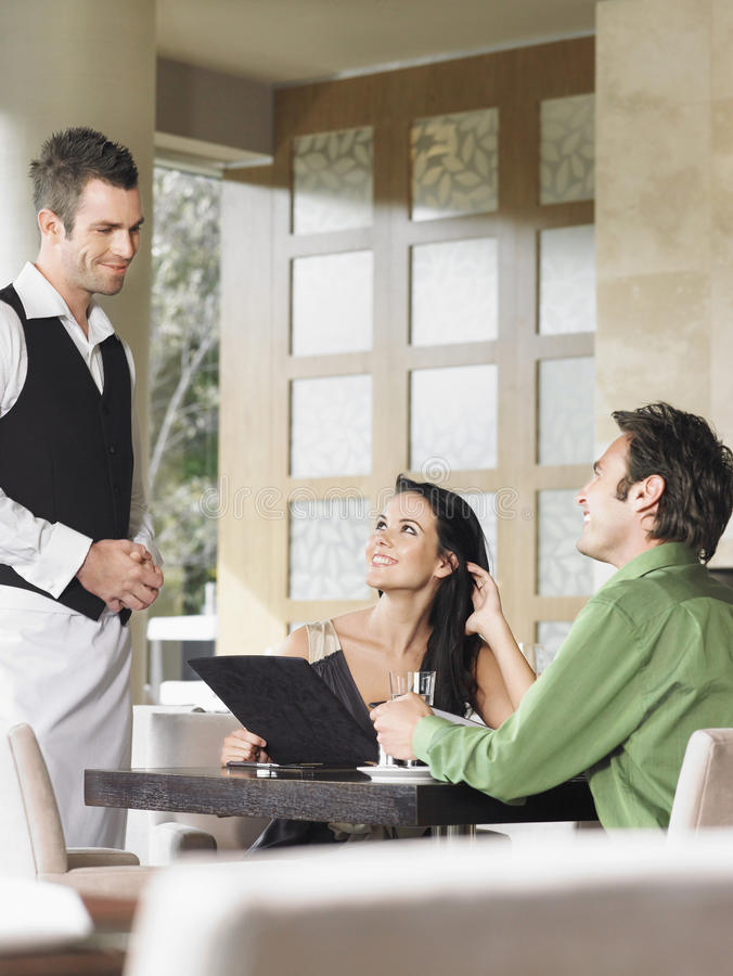 Happy Couple Ordering Meal To Waiter. Happy young couple ordering meal to waiter at outdoor restaurant stock images