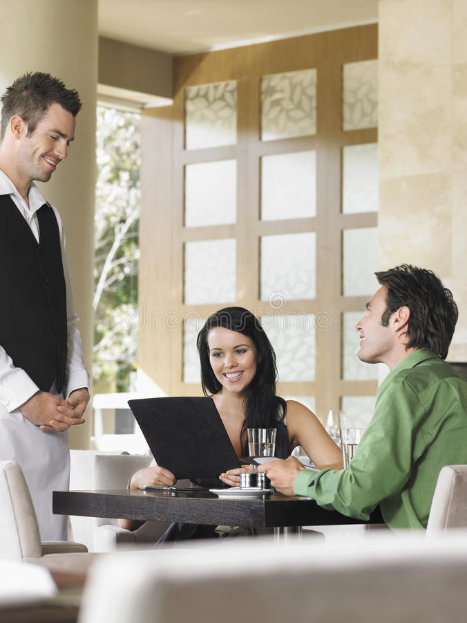 Happy Couple Ordering Meal To Waiter. Happy young couple ordering meal to waiter at outdoor restaurant stock photo