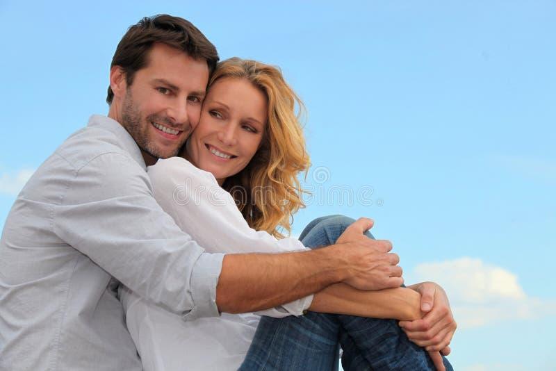 Happy couple outdoors hugging stock photo