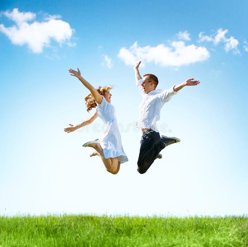 Happy couple outdoors. Happy couple outdoor. Jumping family on green field stock photos
