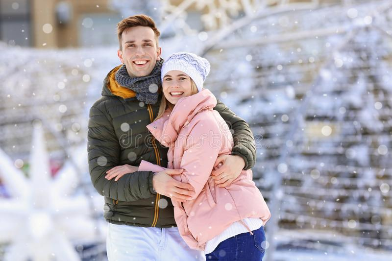 Happy couple outdoors during snowfall on winter day. stock photo