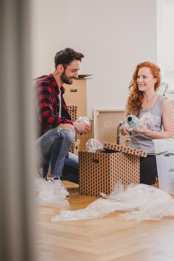 Happy couple packing stuff into a carton box in the interior during relocation stock images