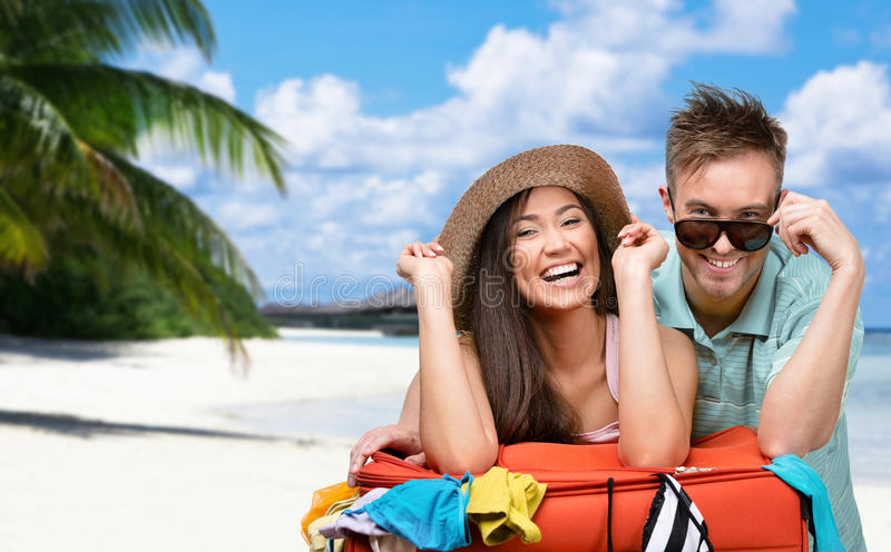 Happy couple packs up suitcase with clothing for traveling royalty free stock images