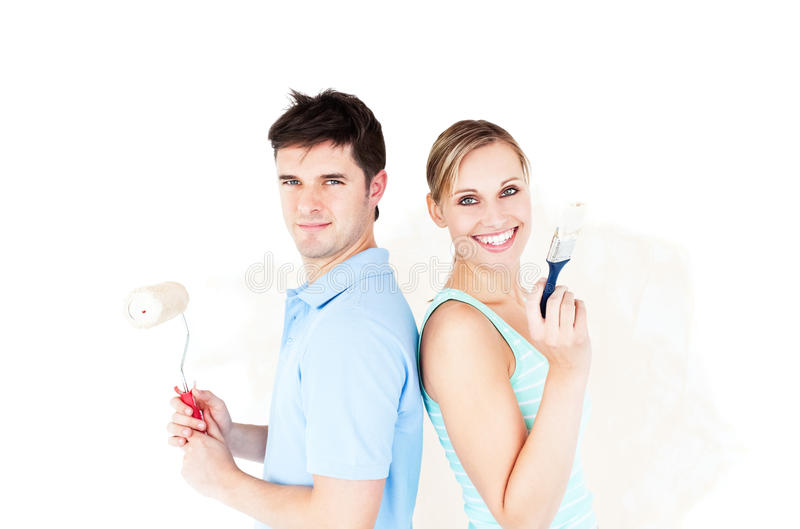 Happy Couple With Paintbrush Standing Back To Back Royalty Free Stock Image