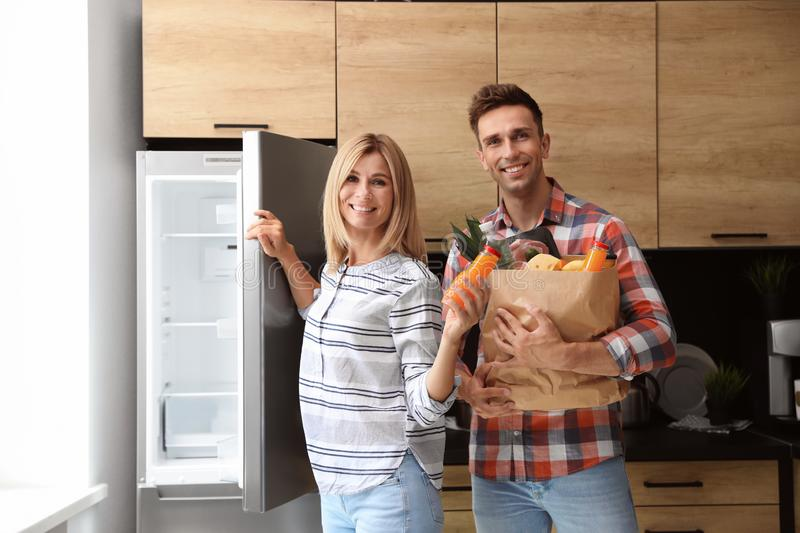Happy couple with paper bag full of products near refrigerator royalty free stock image