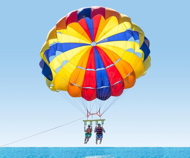 Happy couple Parasailing in Turkey beach in summer. Couple under parachute hanging mid air. Having fun. Tropical Paradise. royalty free stock photo