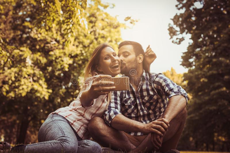 Happy couple in the park. Happy couple taking self-picture with stock images