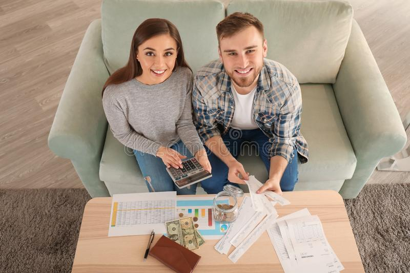 Happy couple with pay bills, calculator and money counting expenses indoors. Money savings concept stock photos