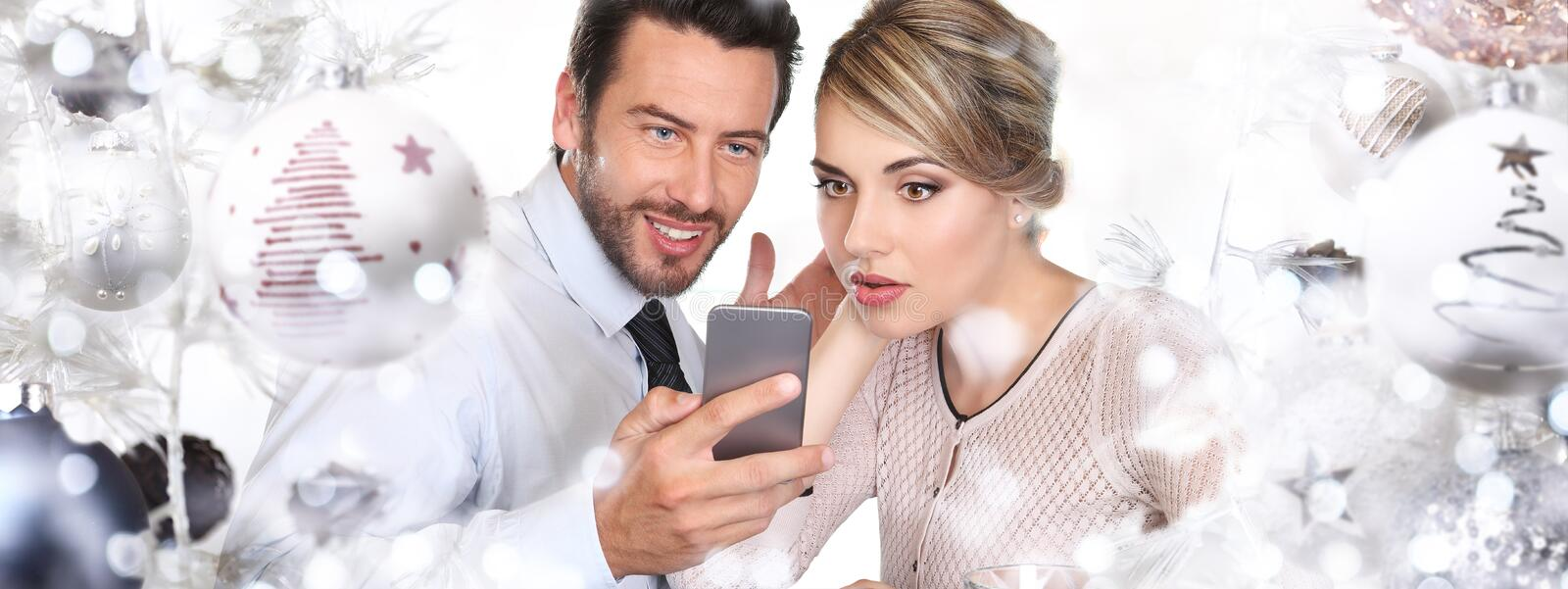 Happy Couple with phone christmas and happy new year event stock images