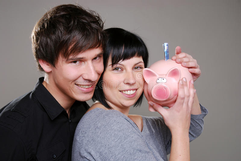 Happy couple with piggybank stock images