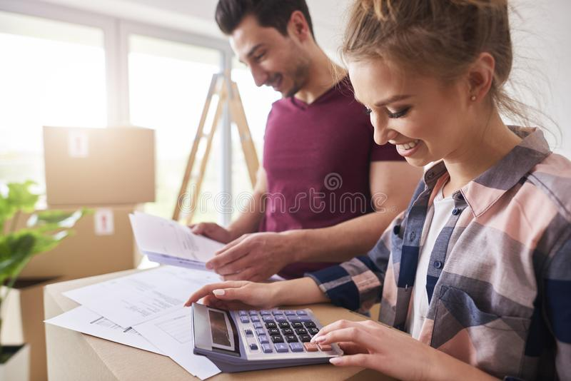Happy couple planning their budget. Next to moving boxes stock images