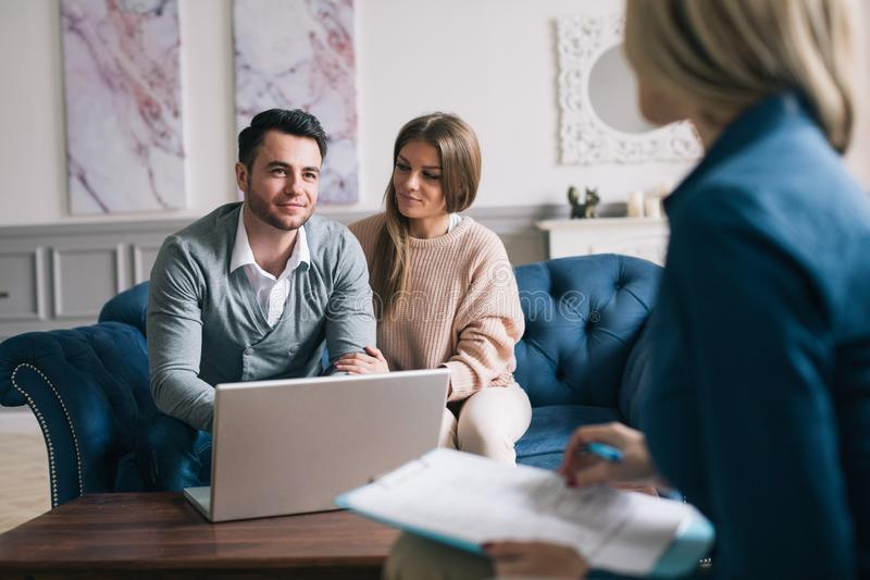 Happy couple planning their future while consulting with insurance agent in their home. Consultation royalty free stock photos